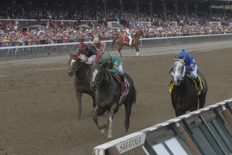 Honor Code, center, overtakes Liam's Map, right, at the wire to win the Whitney Handicap on Saturday at Saratoga Race Course.
