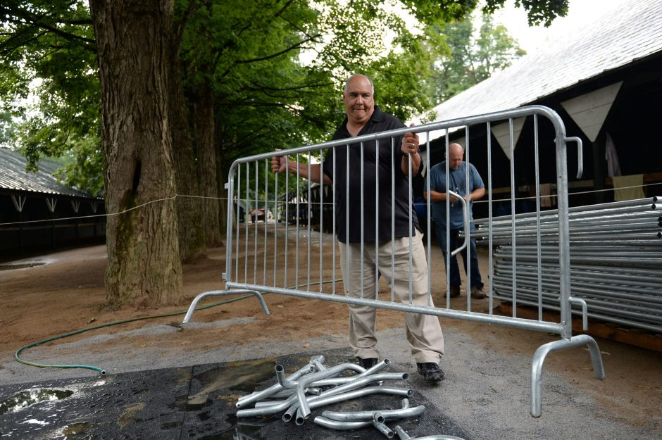 Juan Dominiguez moves a barricade into place outside Terranova Stables in the Saratoga Race Course backstretch Tuesday. Triple Crown winner American Pharoah will be staying in Terranova's barn in preparation for Saturday's Travers.
