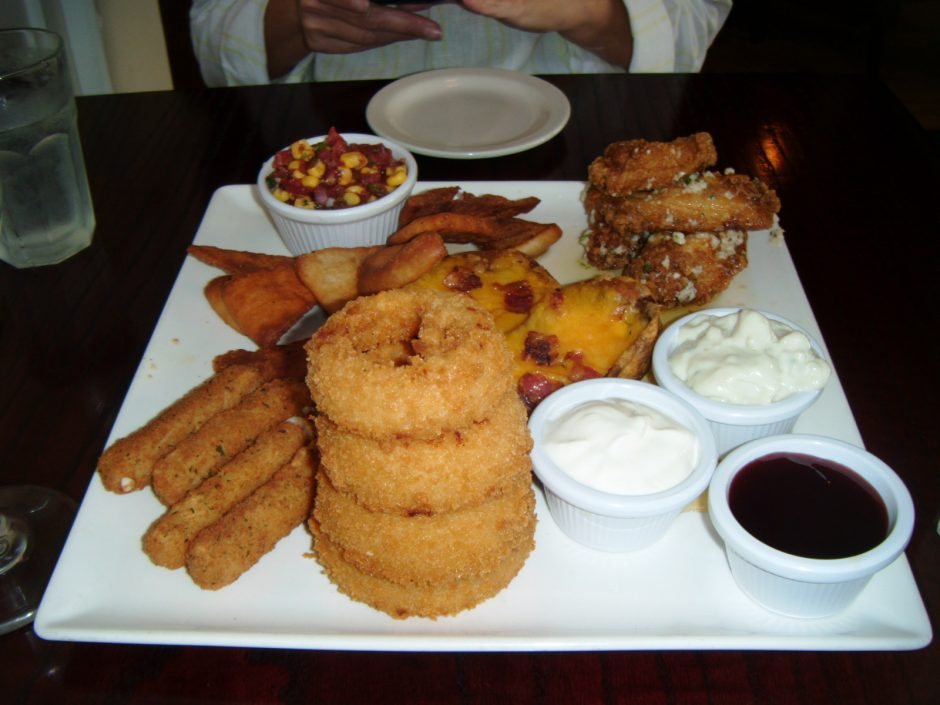 An appetizer sampler platter at Clark's Steakhouse features such diverse treats as onion rings, salsa and potato skins.