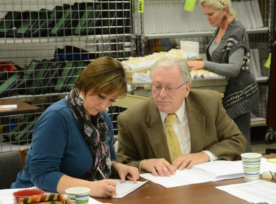Schenectady County Board of Elections Commissioners Amy M. Hild and Art Brassard verify and count absentee ballots for the town of Princetown in November 2014.