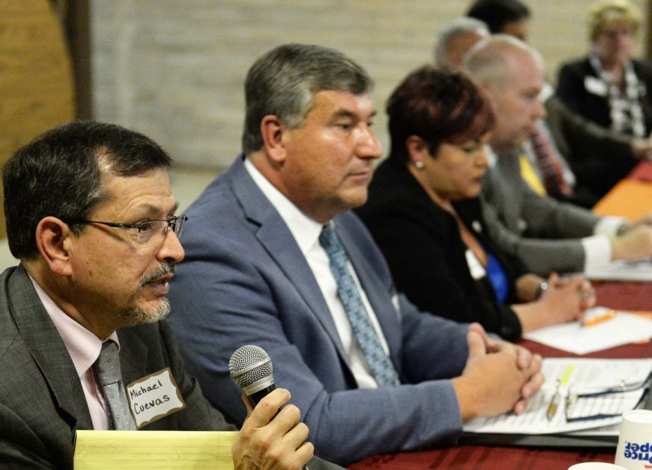 City Council candidate Michael Cuevas answers a question at a debate between 7 candidates on the ballot at 1911 Fairview Avenue in Schenectady Thursday, October 8, 2015. Edward Kosiur sits to his left.