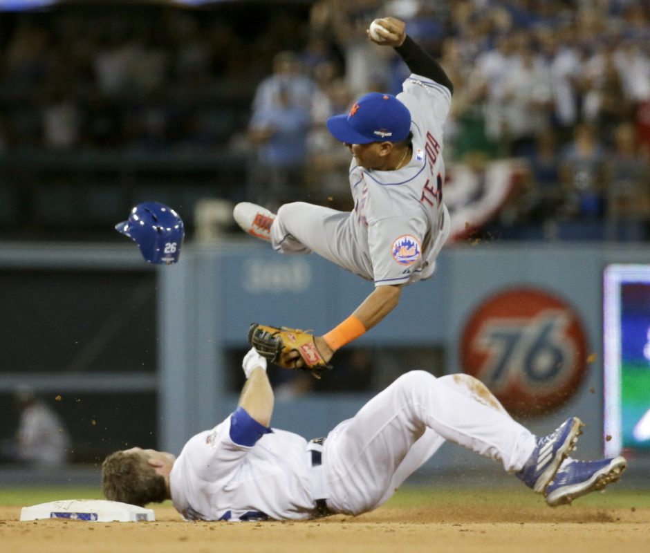 New York Mets shortstop Ruben Tejada, goes over the top of Los Angeles Dodgers' Chase Utley who broke up a double play during the seventh inning in Game 2 of baseball's National League Division Series Saturday. Tejada broke his leg on the play.