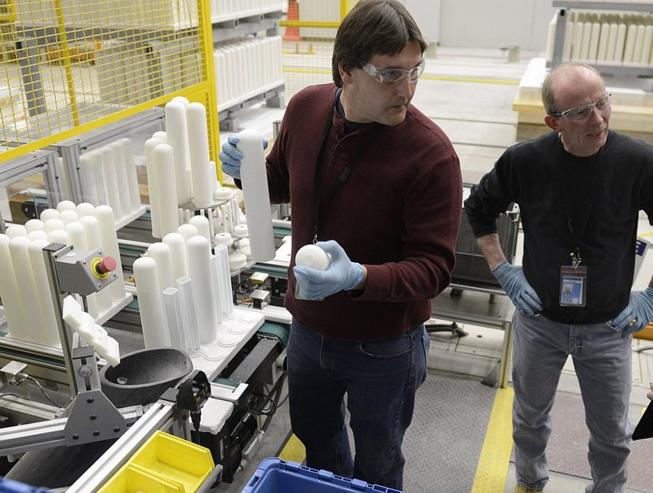 In this 2013 photo, GE workers Daniel Thum, left, and Thomas Yawn, are in the Durathon plant at the Main Campus on Edison Avenue in Schenectady. Thum is holding two of the fifteen ceramic tubes that conduct electrical current inside the battery.