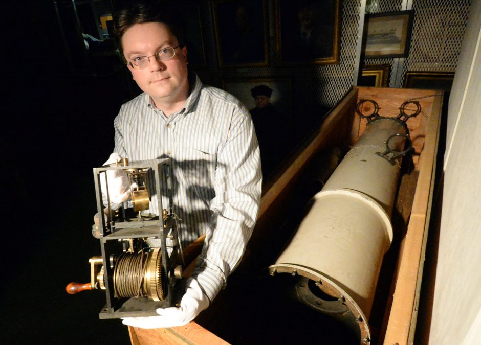 miSci archivist, Josh Hauck, with parts in storage of the Pruyn Brashear Telescope. Hauck holds the clock drive regulator to the telescope. Pictured at the right is the trunk of the telescope.