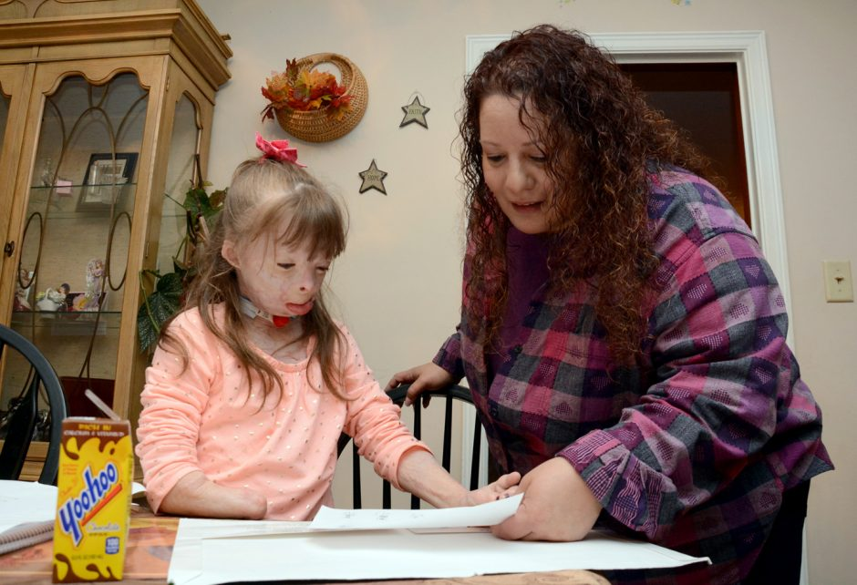 Safyre Terry 8, finishes up her math homework for her aunt, Liz Dolder, to check in this Nov. 18 photo.