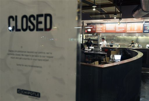 People stand inside a closed Chipotle restaurant in the Cleveland Circle neighborhood of Boston on Monday, Dec. 7, 2015. Boston College officials say 80 students have shown 'gastrointestinal symptoms' since eating at the restaurant.