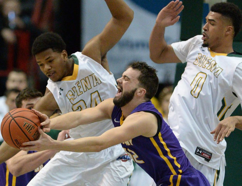 Peter Hooley of UAlbany makes a pass in front of Lavon Long and Javion Ogunyemi of Siena during the Albany Cup game Saturday at the Times Union Center in Albany.