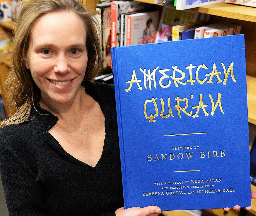 """Open Door Bookstore general manager Amy Lane holds a copy of """"American Qur'an"""" in the Schenectady shop on Wednesday, December 23, 2015."""