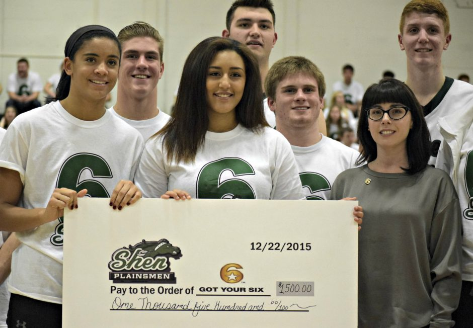 Shenendehowa students present Got Your 6 representative Kate Hoit, front right, with a donation during a boys' basketball game Tuesday.