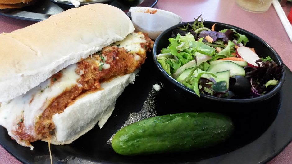 Gershon's Chicken Parm sandwich, on fresh sub roll from Perreca's bakery in Schenectady, comes with a salad of mesclun, green pepper, black olives, cucumber and radish.  (CAROLINE LEE PHOTO)