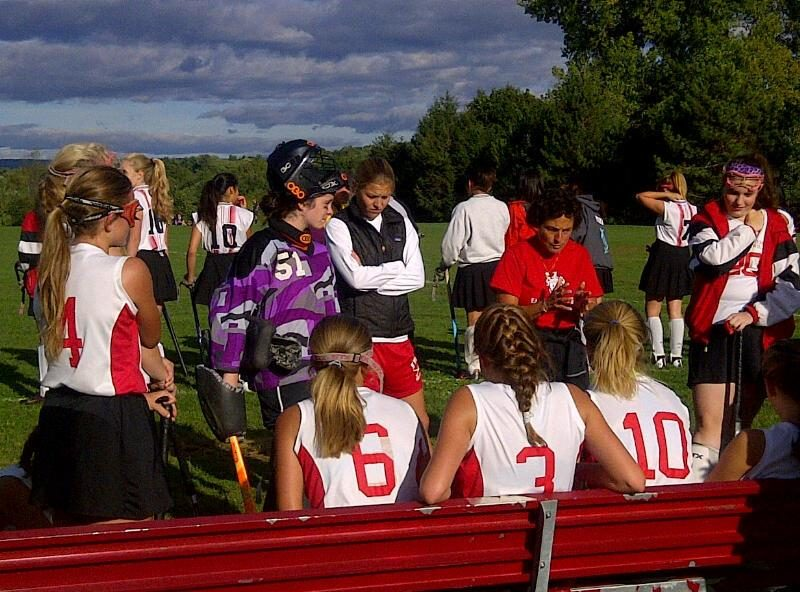 Emma Willard field hockey and lacrosse coach Liz Parry (in red) has a combined 65 seasons coaching teams at the school. She is one of the declining number of coaches helming two varsity sports. 'You're seeing fewer of them,' she said.