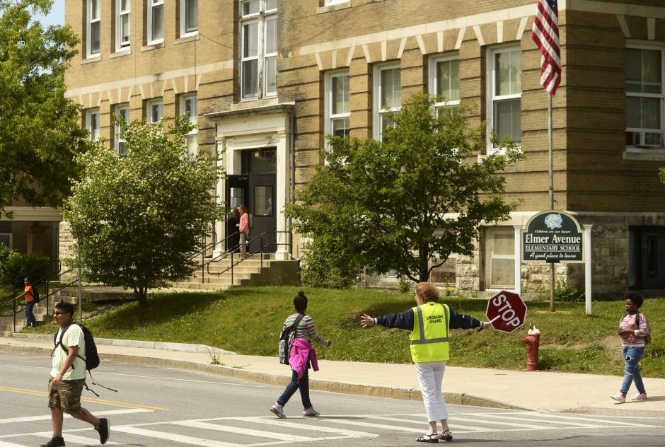 A crossing guard assists students at dismissal last week at Elmer Avenue Elementary School in Schenectady.