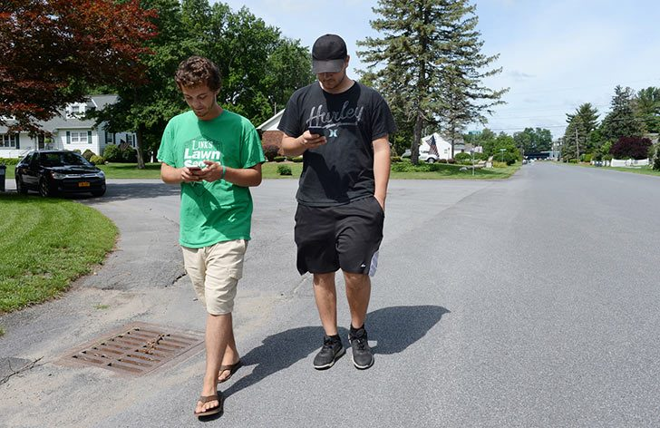 Zach Hotaling and Tom Beerle with their Pokemon Go applications on along Miles Standish Road in Rotterdam.