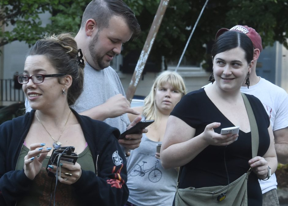 Pokemon Go players watch their smartphones at South Church and Front streets in Schenectady's Stockade neighborhood on Tuesday.
