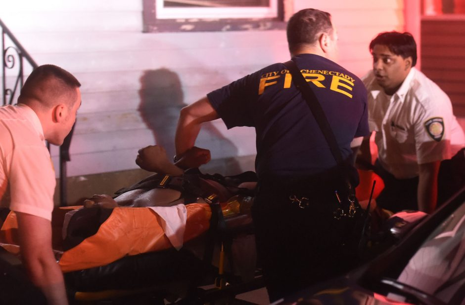 Schenectady Fire paramedics and Mohawk Ambulance personnel move a patient shot in the stomach at 22 Catherine Street to an ambulance Wednesday, August 31, 2016.