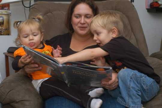 Jaime Pawlinga reads to her children, Samantha and Thomas, as they relax at home in Schenectady on Wednesday evening.