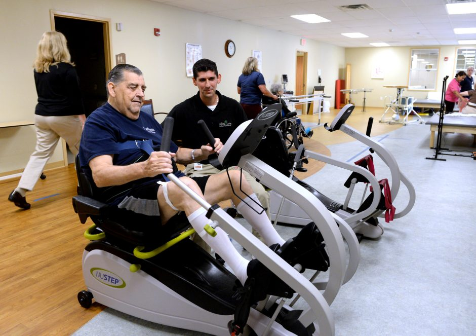 """Physical therapist Brian Reese, center, works on endurance exerciser with """"Steve,"""" left, at Capital Living Nursing and Rehabilitation Center."""