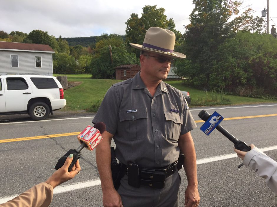 An officer gives a statement at the scene of the search on Sunday.