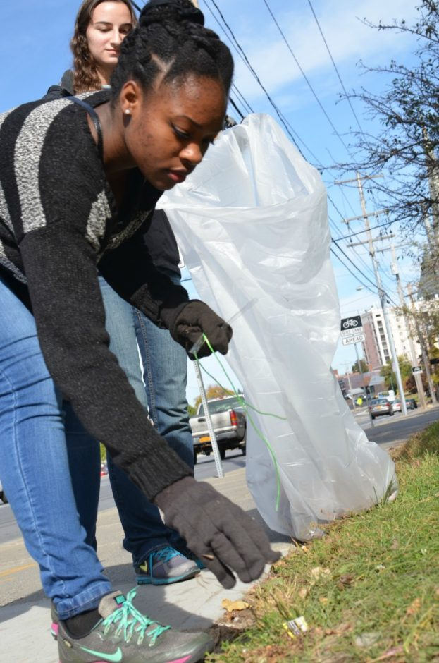 Union College students Kelly Ijang, foreground, and Allison King clean up litter in front of Vale Park in Schenectady as part of the college's 22nd Annual John Calvin Toll Day.