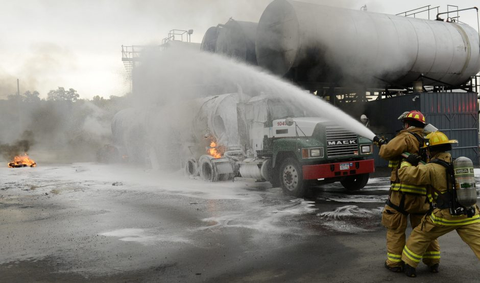 Firefighters spray foam on a tanker truck that exploded behind Water's Edge Restaurant on Freeman's Bridge Road in Glenville Monday, October 17, 2016.