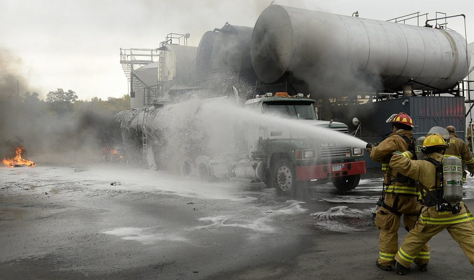 Stratton Air Guard firefighters spray foam on a tanker truck that exploded behind Water's Edge Restaurant on Freeman's Bridge Road in Glenville Monday, October 17, 2016.