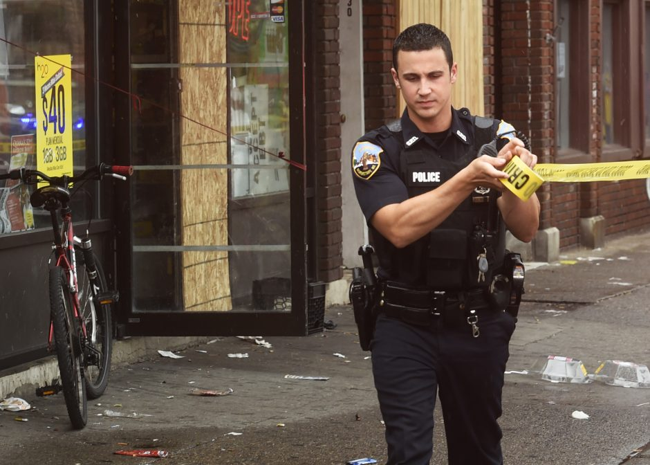 A Schenectady Police officer stretches crime scene tape in front of Chubby's Pizza & Deli on Crane Street after a shooting around 3 p.m. August 14.