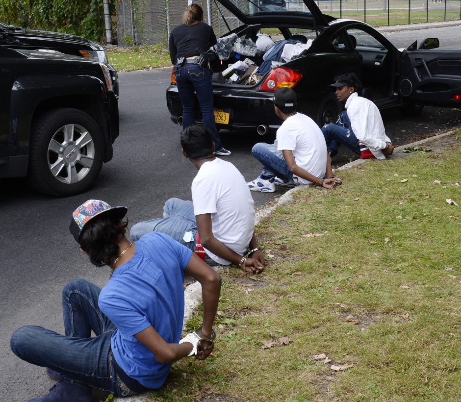 United States Postal inspectors go through a vehicle on Grand Boulevard where these youths were suspected of mail theft on September 30.