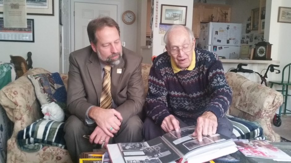 Brian Merriam of Schenectady and his father, Charlie, review Charlie's World War II scrapbook recently.