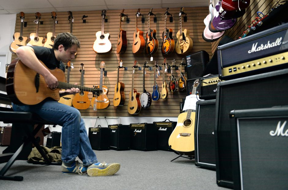 Jeff Valla plays a guitar in Hermie's Music on Jay Street in April. Hermie's is relocating to the Arcade at Proctors.