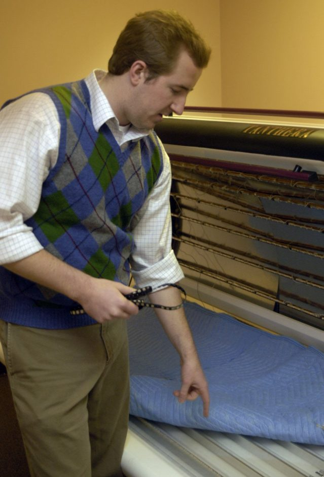 Chris Macomber shows the prototype of the tanning bed he designed with his business partner, Peter Fiset.