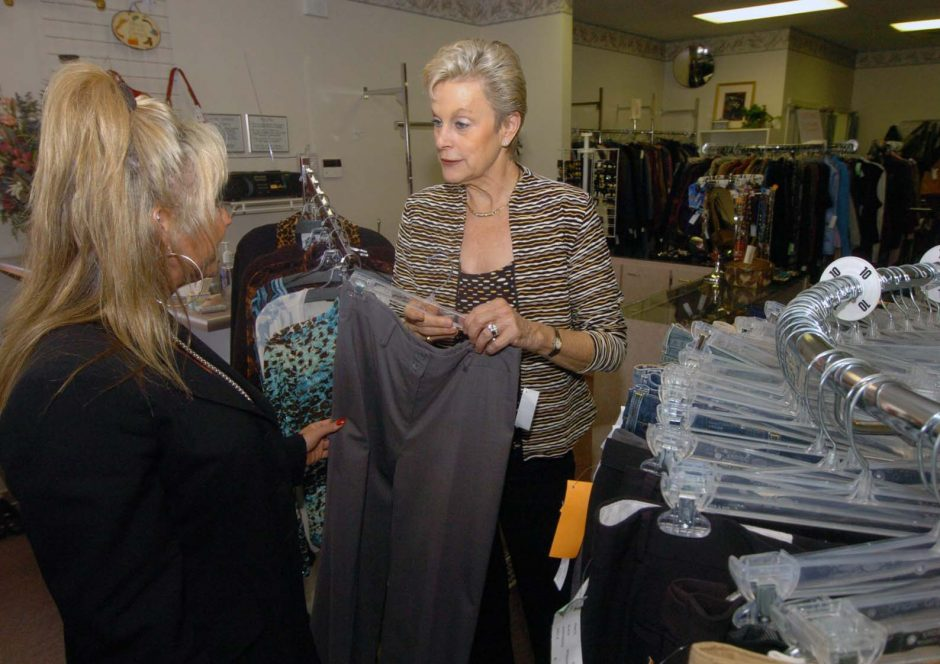 Tracey Harris, right, owner of Worth Repeating, a women's clothing store in Scotia, helps Linda Vasko with her shopping.