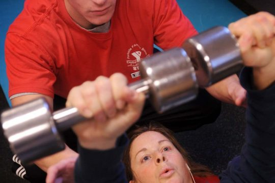 Personal trainer Justin Palermo assists Allison Moran of Glenville with exercises at the Greater Glenville YMCA recently.