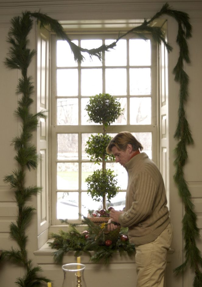 Volunteer Dan Czech of Amsterdam decorates one of the first-floor windows at Old Fort Johnson Monday.
