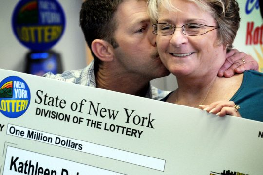 Kathleen Dobson of Amsterdam gets a kiss from her husband Jeff after receiving a ceremonial check for $1,000,000 Wednesday morning at the New York State Lottery Building in Schenectady.