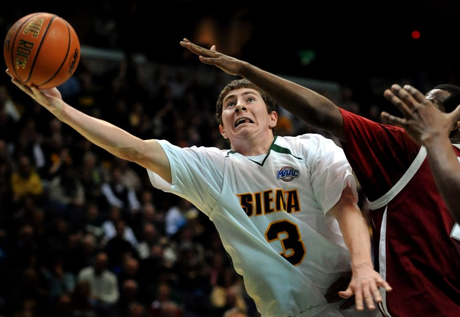 Siena's Kyle Downey, left, stretches out to make a shot while being blocked by Rider's Mike Ringgold Friday.