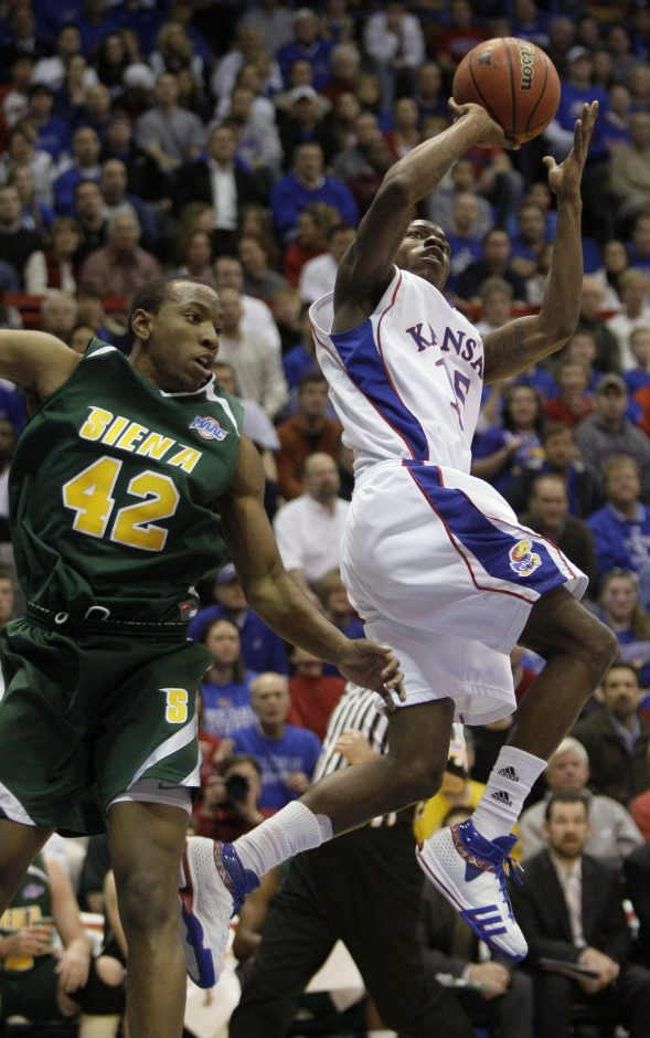 Siena's Alex Franklin, left, keeps an eye on Sherron Collins of Kansas in their non-conference game  Tuesday in Lawrence, Kan. -(AP Photo/Charlie Riedel)