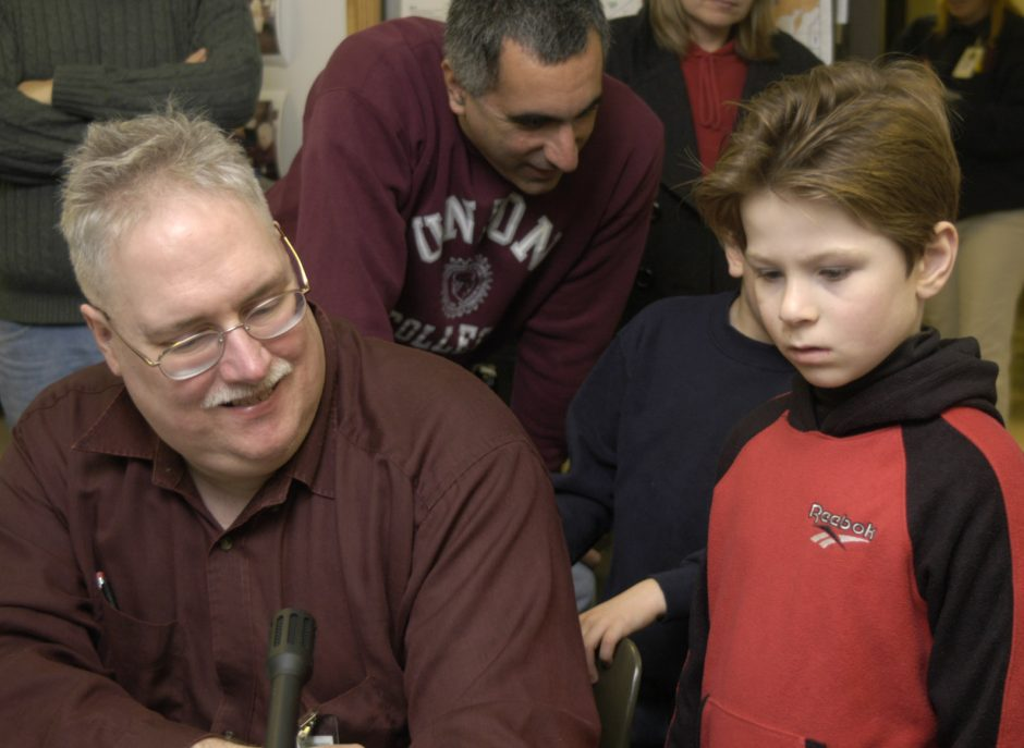 Spencer Moon, 8, of Latham, right, watches as Schenectady Museum Amateur Radio Association (SMARA) member Gerald Murray waits for a gap in conversation so that Moon may hop onto the frequency and say hello to other kids via the amateur radio at the Schene