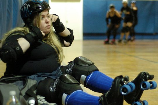 Karen Riley, aka Sin and Tonic, dons her helmet as practice for the Albany All-Stars roller derby team gets under way Thursday night in Troy.