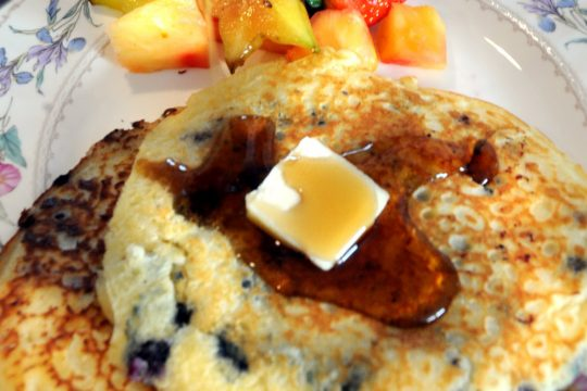 Pure maple syrup is poured over chocolate chip and blueberry pancakes prepared by Amy Cantor of The Omelette King Catering Company in Saratoga Springs.