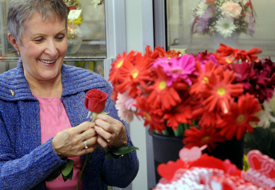 Joyce McDuffee prepares a red rose for an arrangement at Lohse Florist on East State Street in Gloversville on Tuesday.