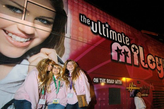 Courtney Castanza, left, Christina Quinn, center, and Lindsay Mayrose, right, all 15 and of Staten Island, have their photograph taken in front of a Miley Cyrus tour bus outside the Times Union Center in Albany on Wednesday.