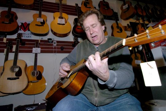 Matt McCabe, owner of Saratoga Guitar on Broadway in Saratoga Springs and the city's former finance commissioner, plays a tune in his store last week.