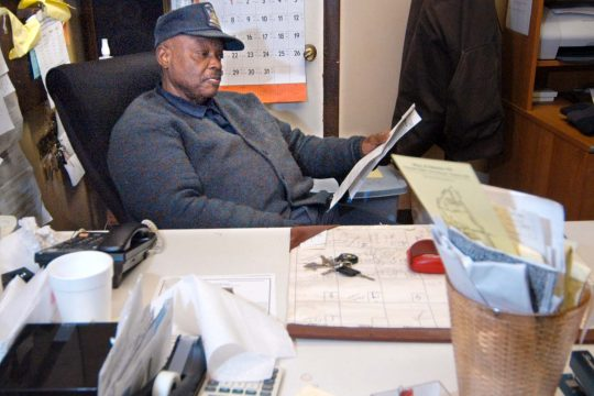 Freddie Anderson of Anderson's Black Top and Sealcoat sits at his office desk Monday evening at 838 State St. The city offered Anderson about half of what wants for his property.