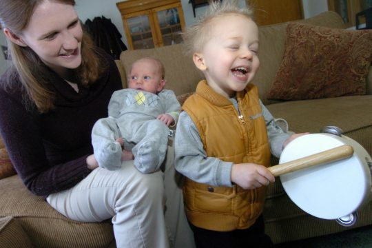 Christian Cail, 2, bangs on his tambourine with his mother Becket and younger brother Caleb at their home on Wednesday afternoon.