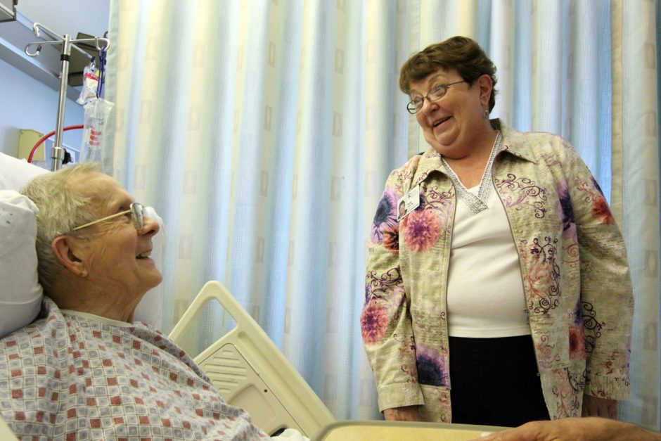 Parish nurse Elizabeth Parks visits Ramond Caouette, a parishioner of the Church of the Immaculate Conception in Glenville, at Ellis Hospital in Schenectady on Friday.