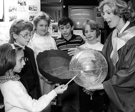 Schoharie Elementary School teacher Kim McCarthy, dressed as the 16th century astronomer Nicolaus Copernicus, holds a model of the universe in 1987.