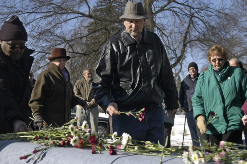 """Larry Lonczak of the Capital Rescue City Mission, center, and others place flowers on the casket of the late William """"Bob"""" Pearce on Monday in Schenectady's Vale Cemetery."""