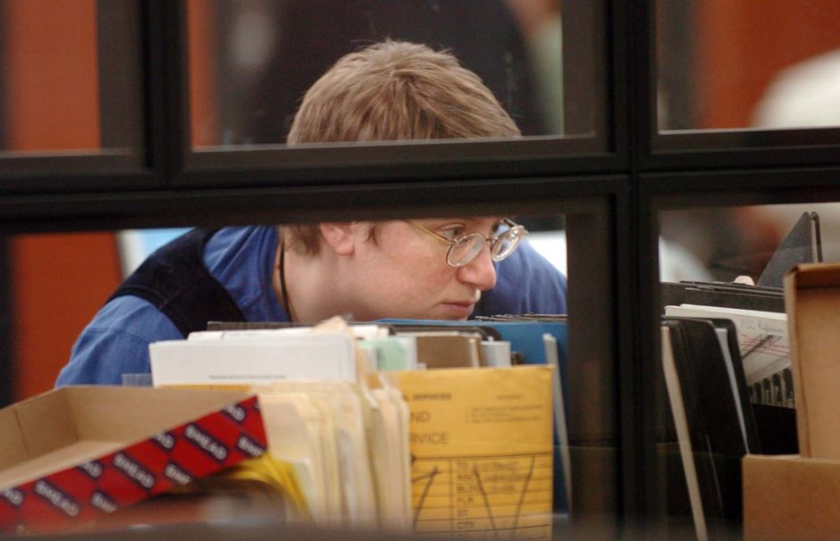 An unidentified woman looks through documents at the New York State Archives Research Room in Albany on Monday.