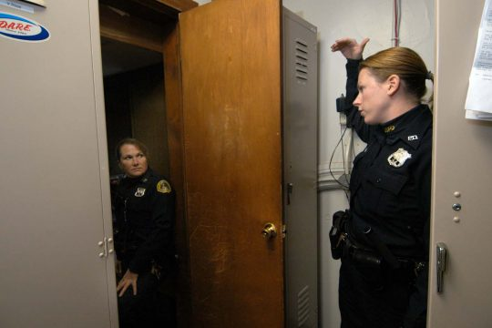 Saratoga Springs police Officer Laura Emanatian, right, talks with Officer Eileen Cotter as Emanatian stands in the department's locker room for female officers.