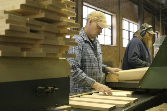 Mill Services employee Tom Marino, center, places pieces of cut wood into the feeder to be finger jointed then glued at the factory in Cobleskill Tuesday.